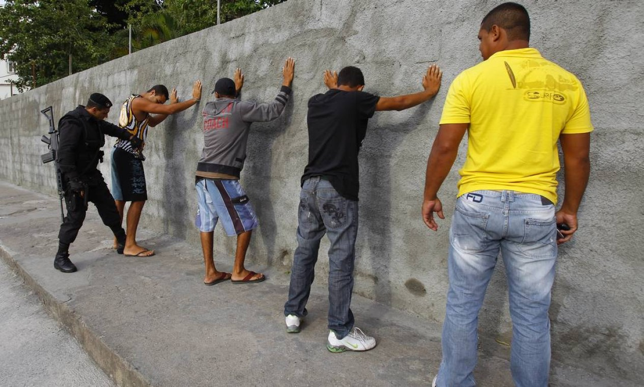 Homens são revistas pela polícia no complexo de favelas Foto: Fernando Quevedo / O Globo
