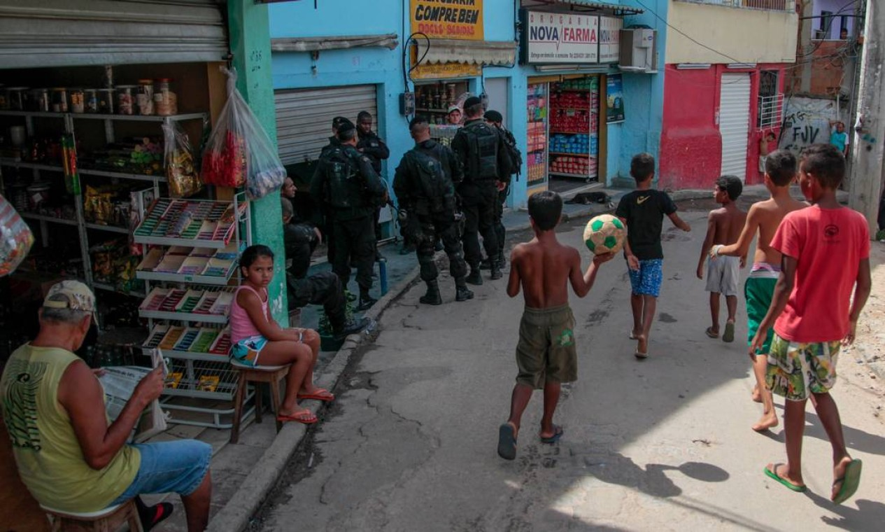 O comércio na região funciona normalmente. Na foto, crianças brincam em uma rua do complexo de favelas Foto: Pedro Kirilos / O Globo