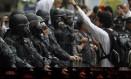 Manifestante enfrenta policiais militares em protesto no Centro do Rio Foto: O Globo / Marcelo Piu