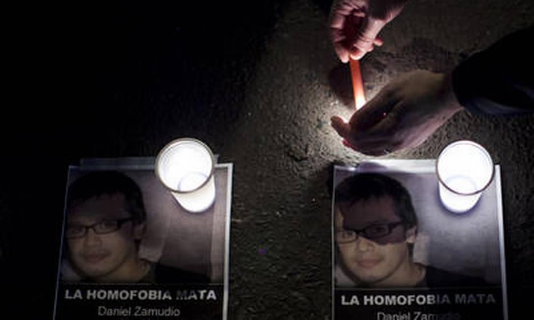 """Homem acende vela junto à embaixada do Chile em Buenos Aires, em protesto contra a morte de Daniel Zamudio; panfleto com a foto da vítima traz a frase """"homofobia mata"""" Foto: Natacha Pisarenko/AP - 30/03/2012"""
