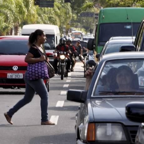 Descuido e risco: a pedestre atravessa no corredor entre os carros na Rua Mário Ribeiro, na Gávea Foto: Marcos Tristão / O Globo