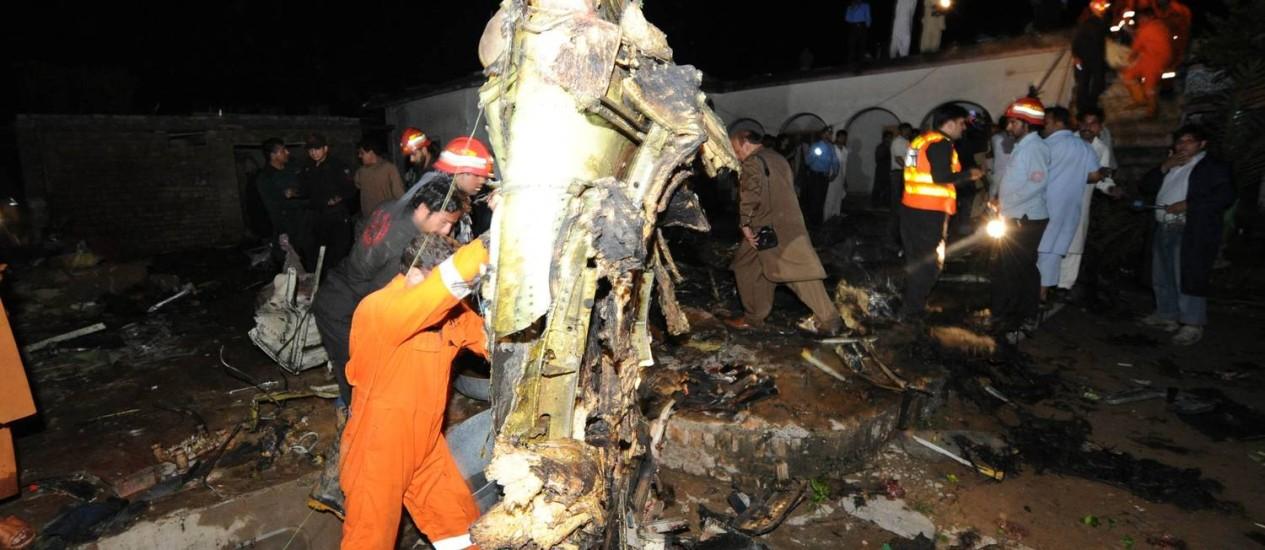 Equipes de resgate trabalham no local em que o avião caiu, em Islamabad Foto: AFP