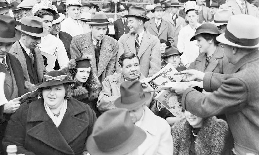 Homem entrega bola para lenda do beisebol James Ruth (no centro), que está acompanhado por sua segunda mulher, Kate Smith