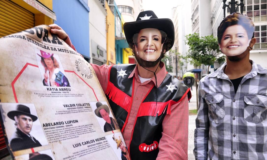 """Em SP, ativistas fantasiados de """"xerife Dilma"""" com cartazes em que parlamentares da bancada ruralista são retratados como foras da lei Foto: Terceiro / Cris Faga"""