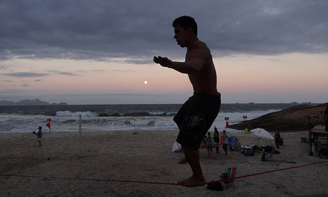 Homem se equilibra em corda, acompanhado no horizone pela lua, em Ipanema Foto do leitor José Conde / Eu-Repórter