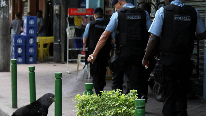 Policiamento reforçado na comunidade após tiroteio entre PMs e traficantes. Agente em patrulha na comunidade lança spray de pimenta em cão Foto: Domingos Peixoto / O Globo