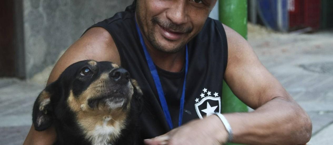 A cadela Pantera, atingida por spray de pimenta, e seu dono, morador da Rocinha Foto: Paula Giolito / Agência O Globo
