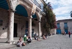 Na praça da Catedral, turistas aproveitam o sol brando do inverno sentados nas calçadas de pedra Foto: Flávia Milhorance / O Globo