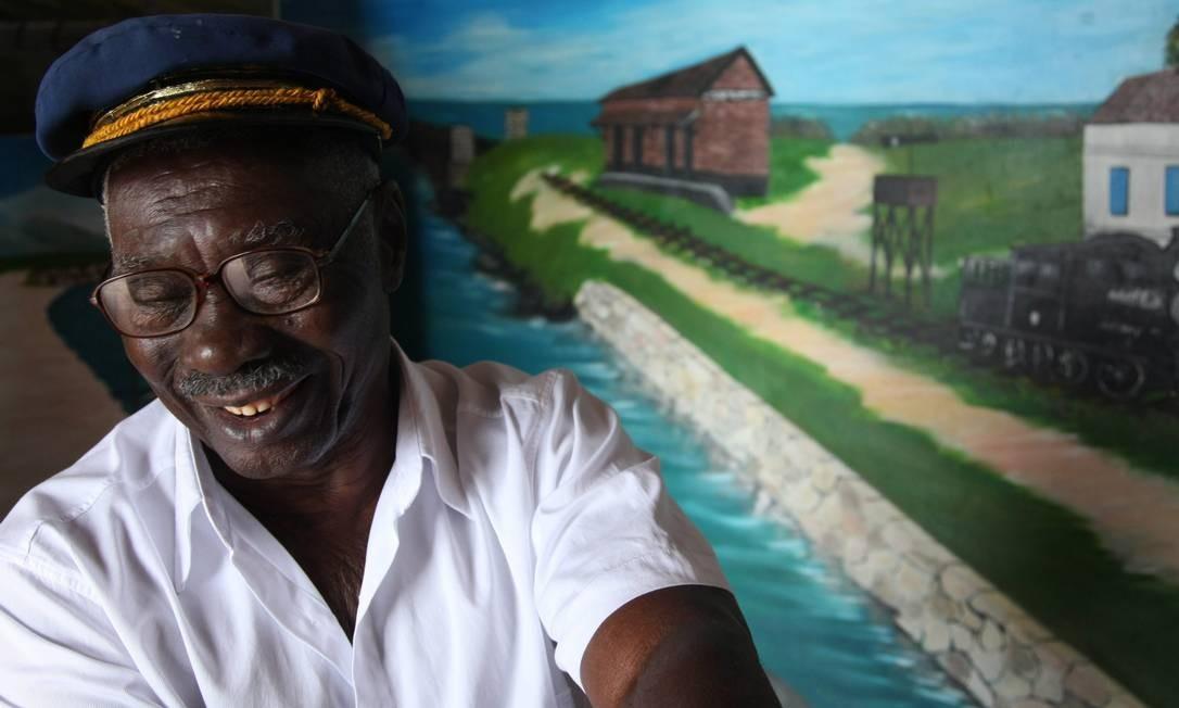 Albertino Miguel, 91 anos, e seu chapéu de maquinista, com uma pintura da primeira estação de trem do Brasil ao fundo Foto: Custódio Coimbra / O Globo