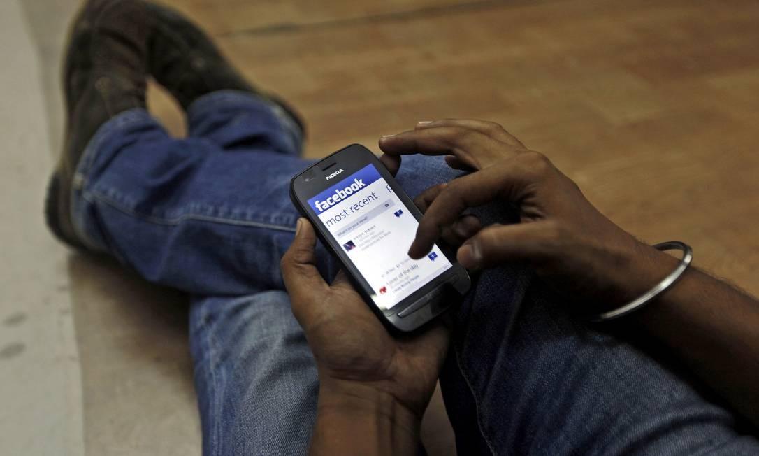 Usuário na Índia testa conexão com o Facebook para celular Foto: AP