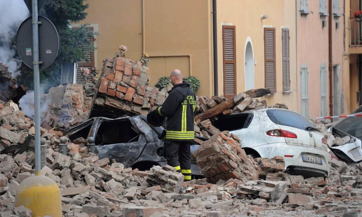 Um bombeiro italiano nos escombros na cidade de Modena, na Itália Foto: Alessandro Fiocchi / AP