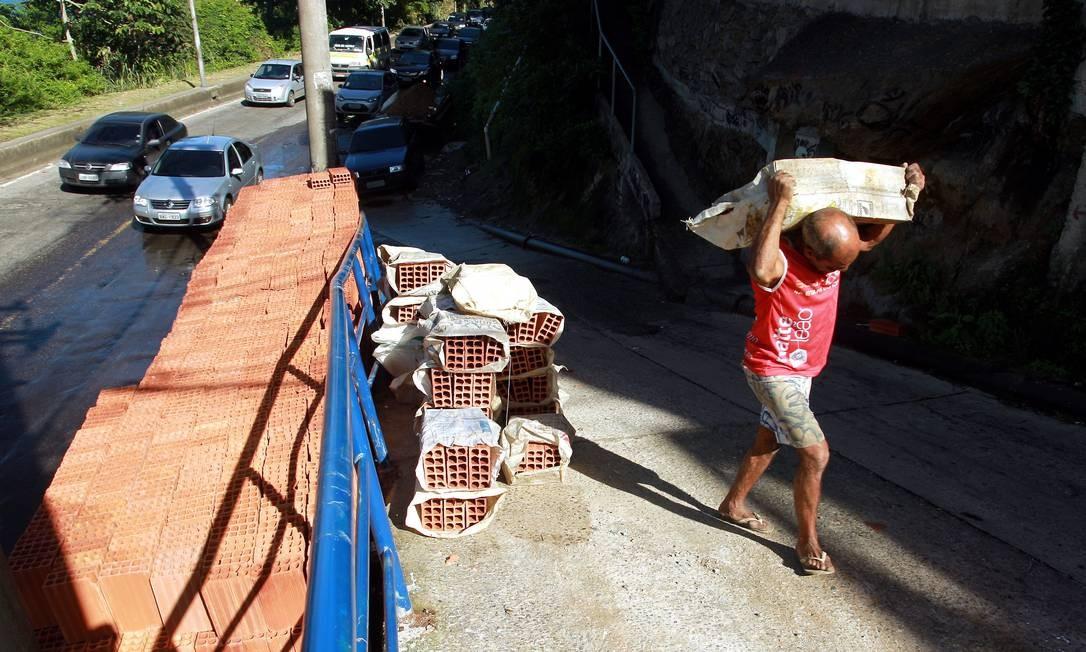 Homem carrega tijolos para o interior do Vidigal Foto: Gabriel de Paiva / O Globo