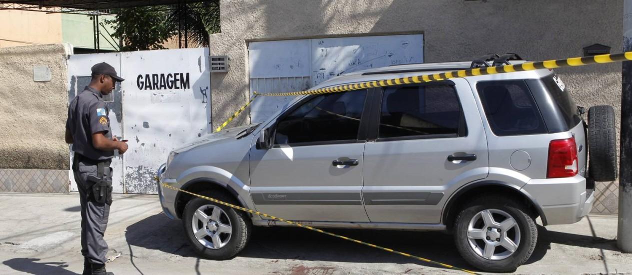 Policial observa o local onde o segurança do prefeito de Mesquita, na Baixada Fluminense, foi morto durante uma tentativa de assalto Foto: Roberto Moreyra / O Globo