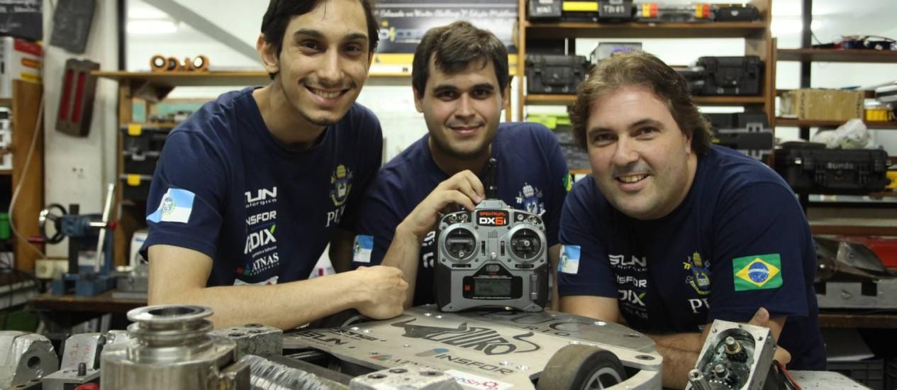 Integrantes da equipe RioBotz, da PUC-Rio, com o robô Touro, campeão dos ringues Foto: Ana Branco