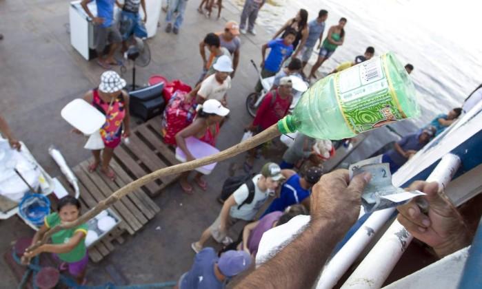 Na cidade de Juriti, pessoas utilizam garrafas pet, presas a cabos de madeira, para vender comida aos passageiros Márcia Foletto / O Globo