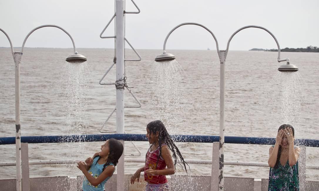 Crianças brincam nos chuveiros do bar do barco: água é puxada do Rio Amazonas por uma bomba Márcia Foletto / O Globo