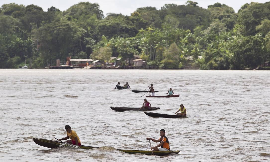 Ao vistar o barco, dezenas de ribeirinhos remam a toda velocidade em busca de donativos Márcia Foletto / O Globo