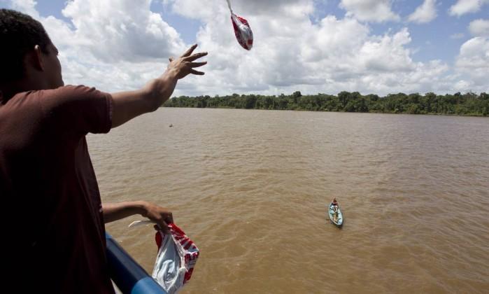 Passageiro joga sacola com roupas para ribeirinhos do estreito de Breves que se aproximam do barco em canoas para pedir doações Márcia Foletto / O Globo