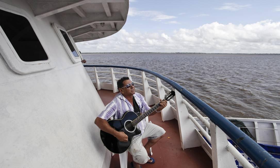 Francisco Brito da Silva toca violão durante a viagem no Rio Amazonas: o cearense foi de barco até Belém de onde pegaria um ônibus para sua terra natal Márcia Foletto / O Globo