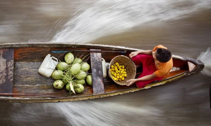 Criança vende frutas em canoa amarrada ao barco, no estreito de Breves Márcia Foletto / O Globo
