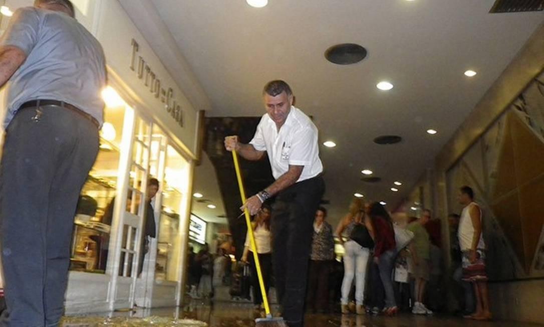 Homem varre os cacos de vidro que ficaram no chão da galeria, em Ipanema Foto: Eu Repórter / Foto do leitor José Conde