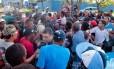 Policial saca a arma para conter tumulto durante a entrega do cartão de indenização para catadores do Aterro de Gramacho