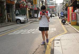 Pelas ruas da capital, é comum ver adolescentes caminhando de olho no celular. A cidade é altamente conectada e wireless. A penetração da internet é de quase 90% Foto: Claudia Sarmento / Agência O Globo