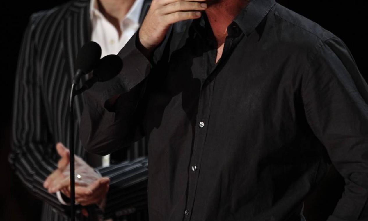 Christian Bale se emocionou com clipe do filme 'The Dark Knight', que trouxe imagens de Heath Ledger, morto em janeiro de 2008, como o Coringa. O ator subiu ao palco para apresentar um novo trailer de 'The Dark Knight Rises' Foto: AP Photo