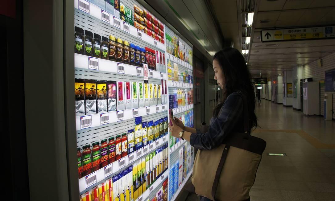Jovem faz compras em supermercado com prateleiras virtuais numa estação de metrô de Seul Foto: Claudia Sarmento / Agência O Globo