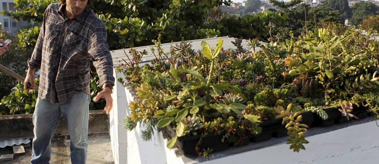 O pesquisador Renato Castiglia junto ao casebre com telhado verde na Fiocruz: experimento já verificou diferença de até cinco graus Celsius na temperatura interna do ambiente Foto: Marcelo Piu