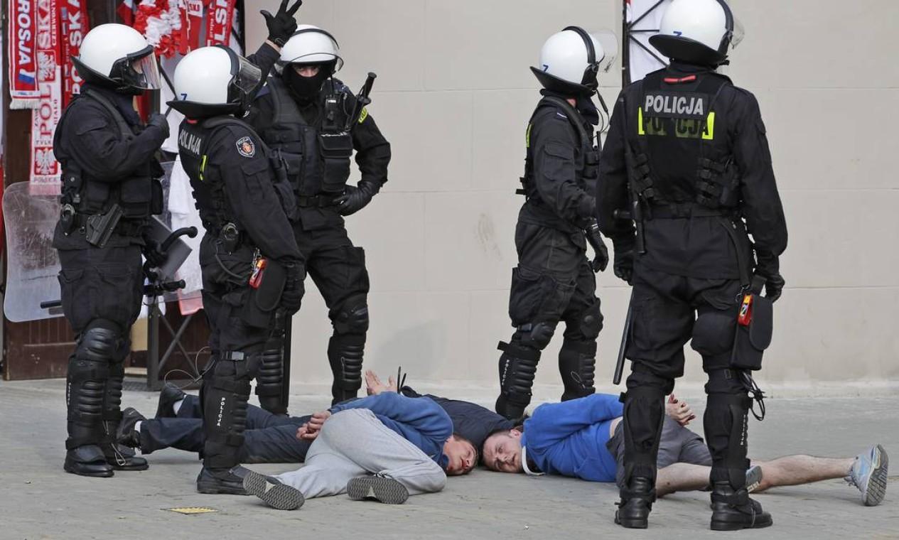 Policiais vigiam torcedores presos durante a briga nas ruas de Varsóvia Foto: AP