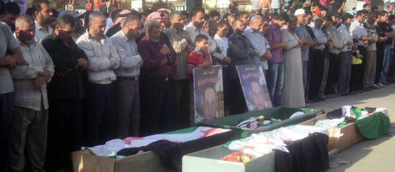 Sírios rezam durante funeral de vítimas do confronto com o governo em Deraa, perto da fronteira com a Jordânia, em imagem divulgada por um grupo opositor Foto: AFP