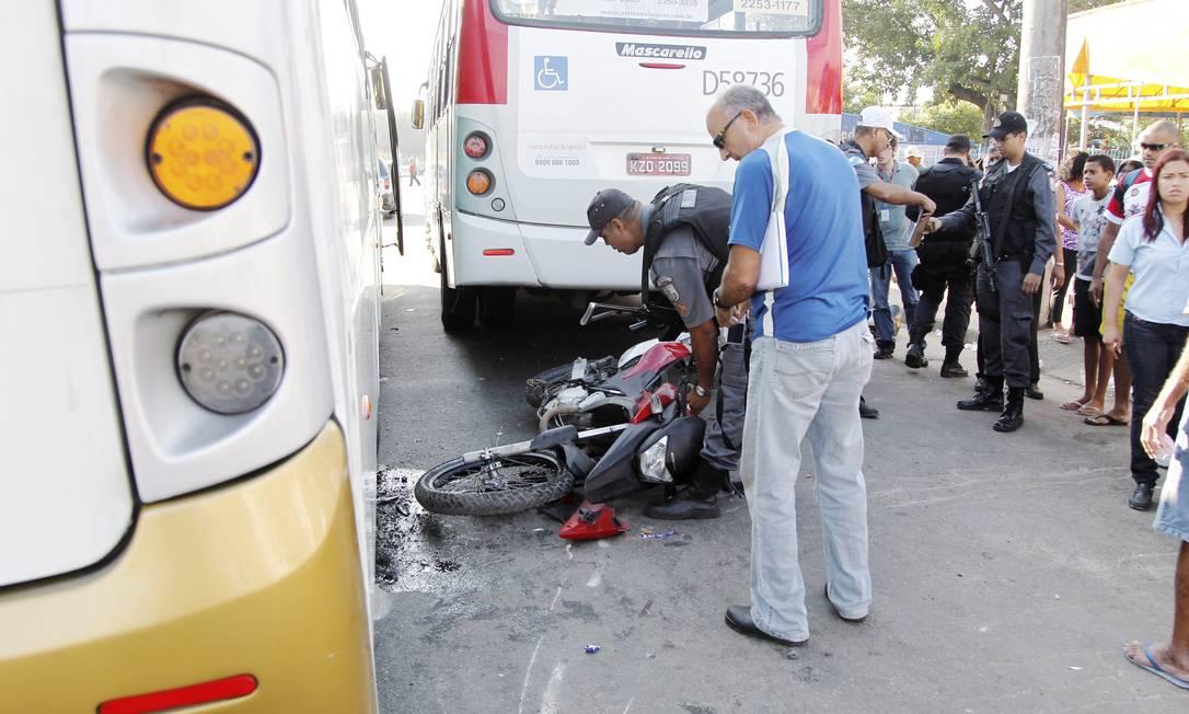 Policial mexe na moto que se envolveu em acidente com dois ônibus na Avenida Brasil, na altura de Vila Kennedy, na Zona Oeste, na manhã desta sexta-feira Bruno Gonzalez / Extra
