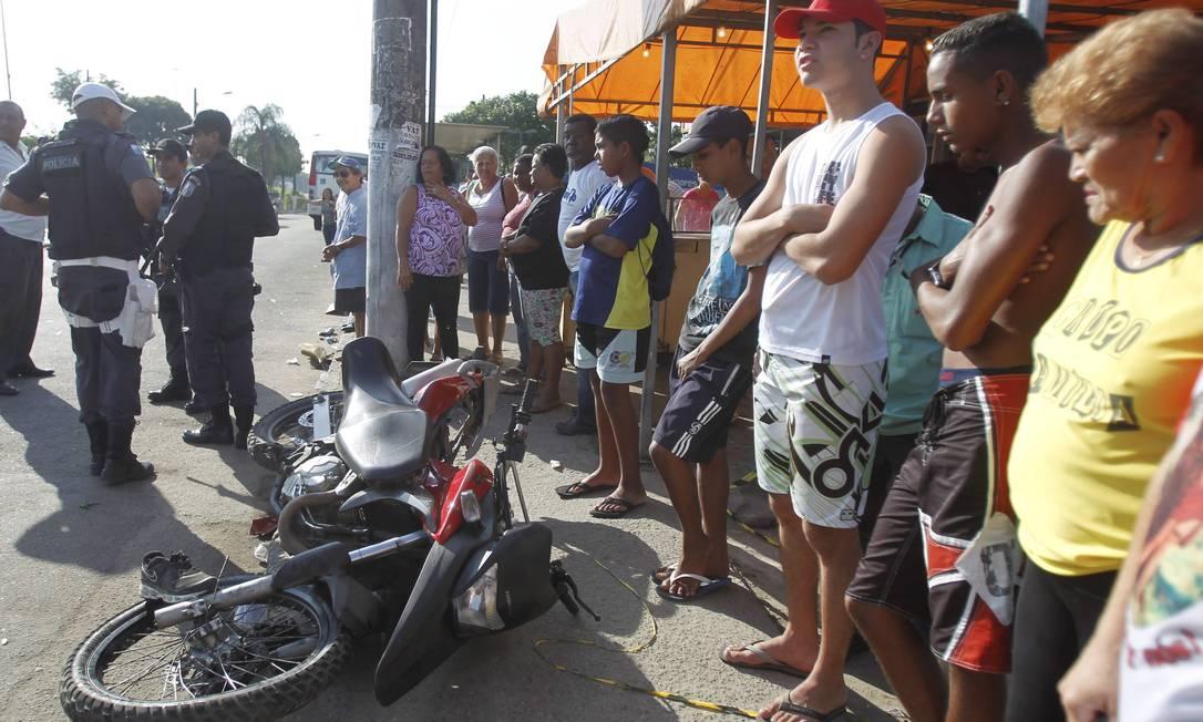 Curiosos observam a moto que atingiu ônibus e acabou atropelando pedestres na calçada Bruno Gonzalez / Extra