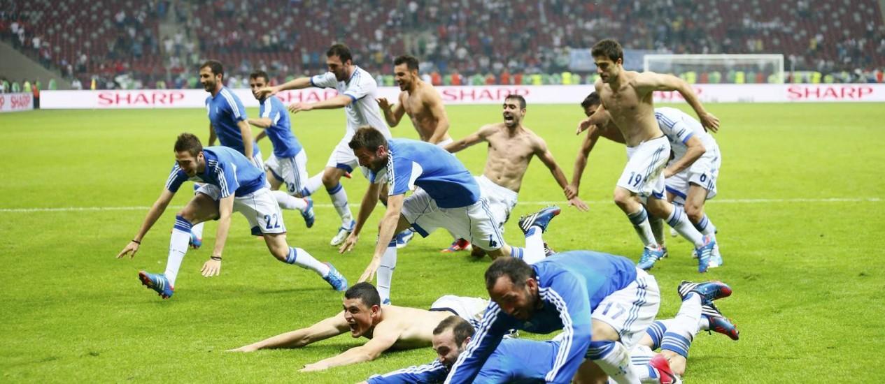 Jogadores gregos mergulham no gramado em Varsóvia para festejar a vaga nas quartas da Eurocopa Foto: Reuters