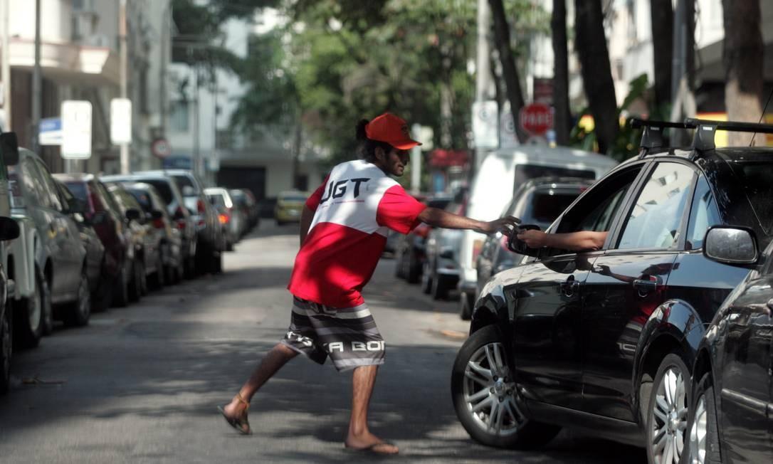 Depois de ter sido flagrado atuando durante a semana, na Rua Ayres Saldanha, em Copacabana (acima), flanelinha continua no mesmo ponto sem ser incomodado (ao lado) Foto: Pedro Teixeira / O Globo
