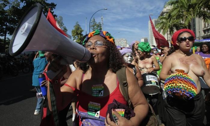 """Com o megafone, manifestante grita frases como """"Meu corpo é meu"""" Sergio Moraes / Reuters"""