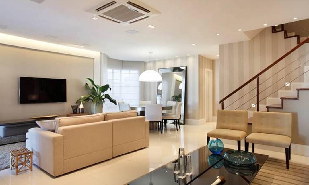 Na sala da casa, papéis de parede liso e listrado: opção pelo bege na decoração, contrastando com cores de adornos, como o vaso da mesinha Divulgação