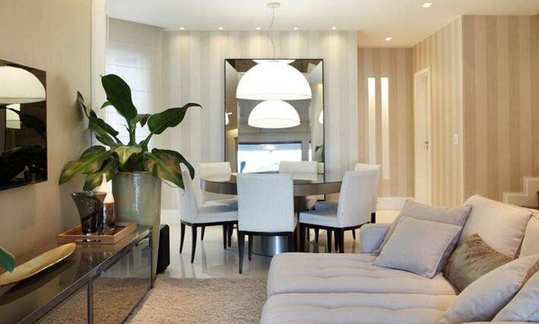 Na sala de jantar, espelho amplia espaço e ajuda a função da luminária que, além de decorativa, ilumina o ambiente de forma difusa Divulgação