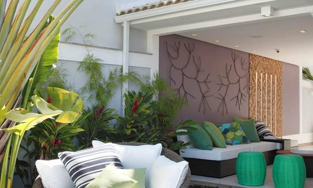 Varanda, de frente para a pequena adega, tem parede cor uva e painel de teca idêntico ao da adega, com rasgos de iluminação Divulgação