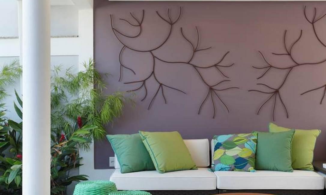 Pufes verdes, feitos de corda náutica, chamam a atenção na varanda, que também exibe escultura de ferro na parede Divulgação