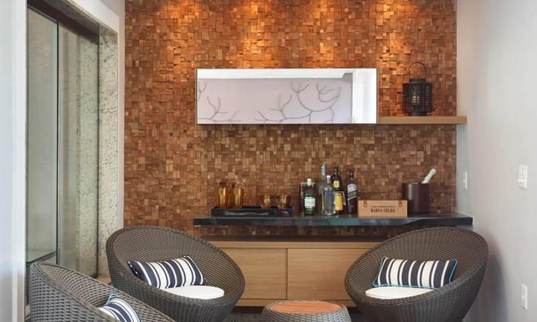 Na varanda, próximo à churrasqueira, a pequena adega: parede revestida de placas de teca com quadradinhos de 5cm por 5cm confere aconchego ao ambiente Divulgação