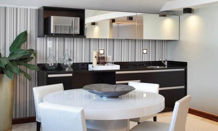 Detalhe do espaço para refeições, no sótão: preto na bancada e papel de parede com listras dão um ar elegante ao local Divulgação