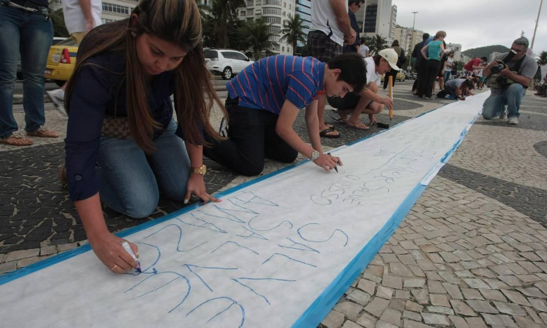 Pedestres escrevem poemas no calçadão de Copacabana Foto: Hudson Pontes / Agência O Globo