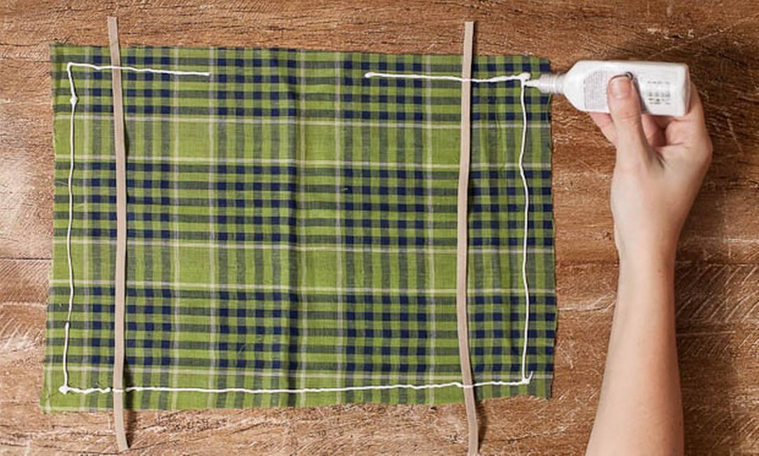 Posicione o tecido de baixo com a parte correta virada pra cima e aplique os elásticos por cima, uns quatro dedos em direção ao centro. Aplique a cola em toda a borda com uma margem de um dedo generoso. Deixe a largura da sua mão sem cola para que você possa colocar o enchimento. A cola é a sua costura, então quanto mais reta e uniforme for a linha da cola, melhor o acabamento. A cola deve ir por cima e por baixo do elástico Divulgação