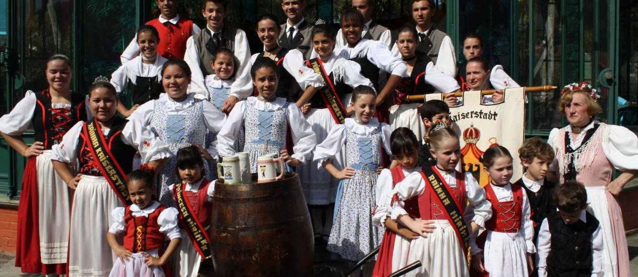 Os integrantes do grupo folclórico Kaiserstadt Kulturkreis posam em frente ao Palácio de Cristal Foto: Foto: Divulgação