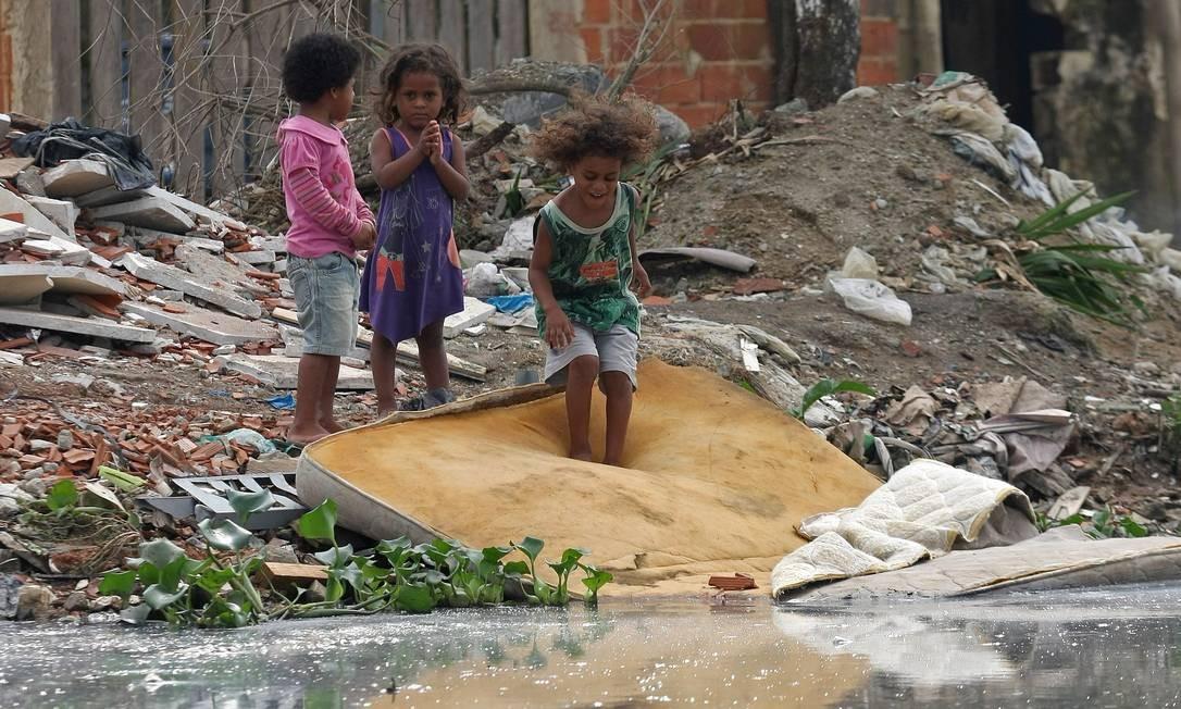 À BEIRA DO RISCO: crianças brincam na margem do Canal do Anil, em Jacarepaguá, região vizinha ao epicentro da Rio+20 Foto: Custódio Coimbra