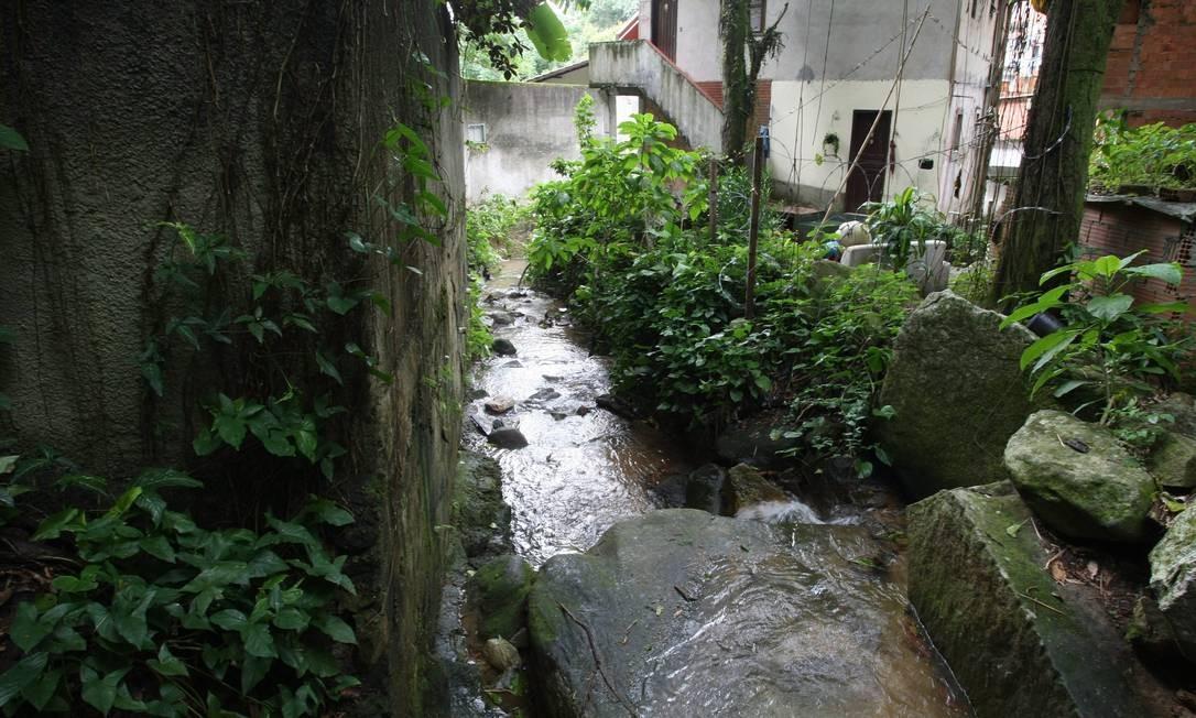 O MEIO: o curso d'água estreitado pela favela dos Guararapes, no Cosme Velho, começa a receber esgoto Foto: Custodio Coimbra