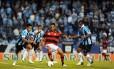 Íbson mata a bola entre dois jogadores do Grêmio