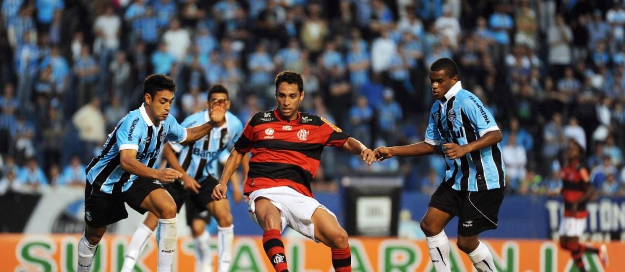 Íbson mata a bola entre dois jogadores do Grêmio Foto: Alexandre Vidal / Fla Imagem/Divulgação